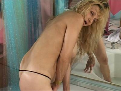 Vollbusige blonde Milf fingert sich die Pussy